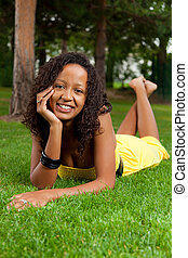 Young black woman lying down on the grass