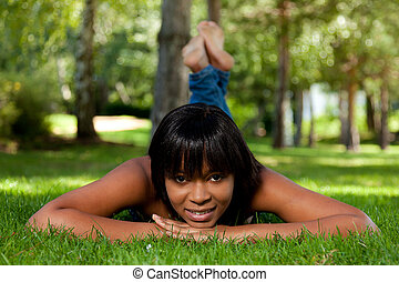 Young black woman lying on the grass