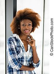 young black woman next to a window