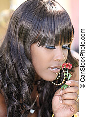 Young black woman outdoors smelling red flower