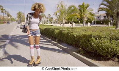 Young black woman roller skating along the road