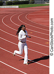Young black woman running on track sweat suit