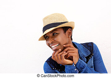 Young black woman smiling against white background with hat