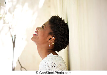 Young black woman smiling and looking up
