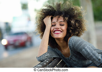 Young black woman with afro hairstyle smiling in urban background. Mixed girl wearing casual clothes.