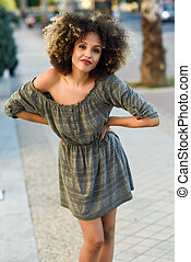 Young black woman with afro hairstyle smiling in urban background