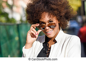 Young black woman with afro hairstyle with aviator...