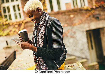 Young black woman with coffee cup and mobile phone on the street
