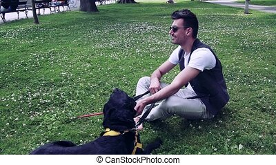 Young blind man with white cane and guide dog sitting in park in city, resting. Slow motion.