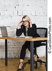 Young blond beauty businesswoman sitting at a office table...