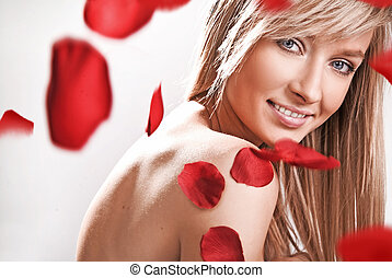 Young blond beauty in spa salon, over rose petals