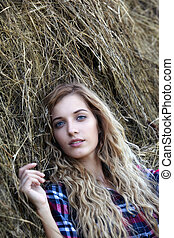Young blond blue-eyed country girl near haystacks