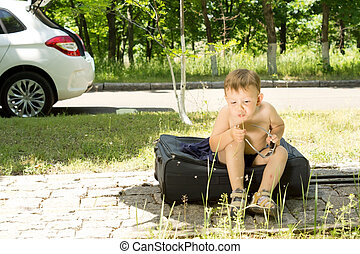 Young blond boy blowing a dandelion outdoors