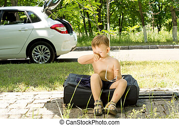 Young blond boy sitting on a travel bag sneezing
