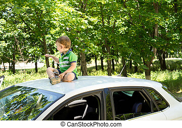 Young blond boy sitting on the rooftop of a car