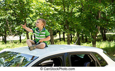 Young blond boy sitting on top of a car pointing