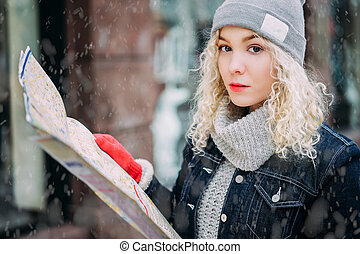 Young blond curly girl with map of London, winter