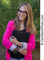 Young blond entrepreneur with a folder with documents in her arms.
