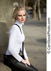 Young blond fashion model posing on the street.