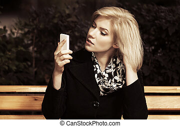 Young blond fashion woman looking at mobile phone