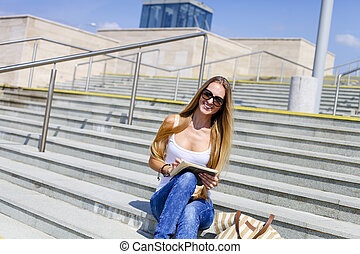 Young blond female college student using tablet computer outdoors
