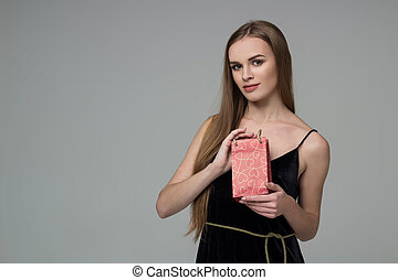Young blond girl in black dress with red present package