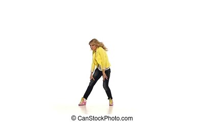 Young blond girl in yellow clothes dancing sexy-jazz on white background, slow motion