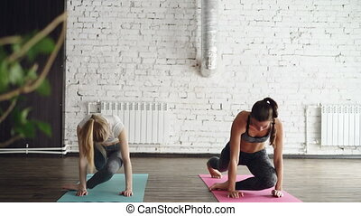 Young blond girl is enjoying individual yoga practice with friendly female instructor in light studio. Women are doing sequence of asanas on bright mats.