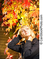Young blond girl on autumn background
