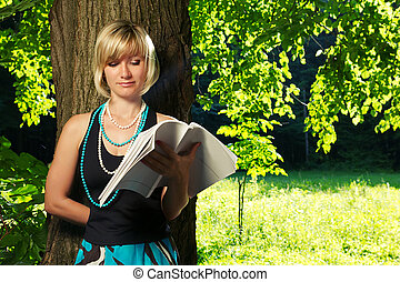 Young blond girl reading book in the nature