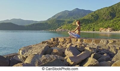 Young Blond Girl Sits in Yoga Pose against Hilly Landscape