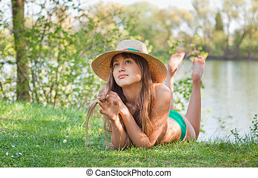 young blond girl with a hat lying on the grass