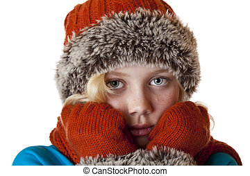 Young blond girl with winter cap and gloves is cold