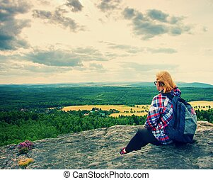 Young blond hair Woman hiker takes a rest on peak of the Mountain