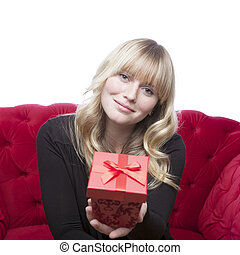 young blond haired girl has a present box for you on red sofa in front of white background