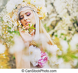Young blond lady in the fragrant garden