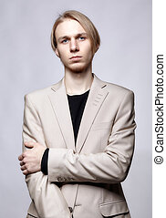 Young blond male model in beige man suit