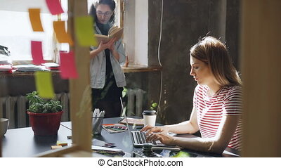 Young blond student wearing casual clothes is busy typing on laptop while her friend is reading book standing near window. Loft style apartment is in background.
