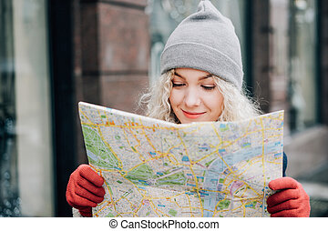 Young blond tourist curly girl with map of London, winter