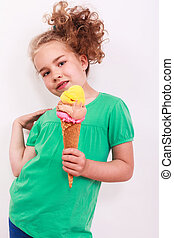 Young blond girl with ice-cream cone in the hand you from the body away holds and curly hair is in the pose with look in the camera.