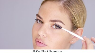 Young blond woman applying mascara with a brush - Young...