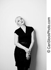 young blond woman black dress against white wall
