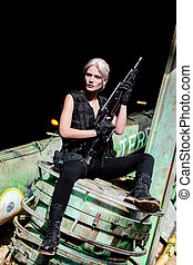Young blond woman carrying a paintball weapon