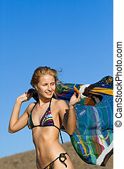 young blond woman dancing with kerchief against the blue sky