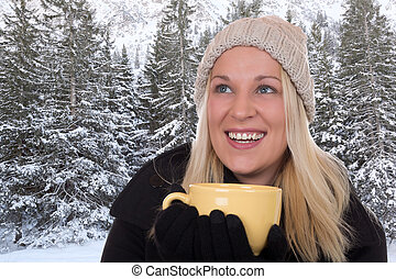 Young blond woman drinking outdoors in winter cup of tea
