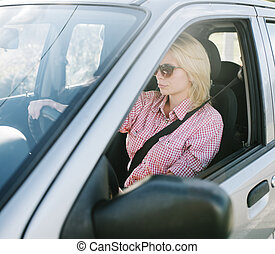 Young blond woman driving a car.