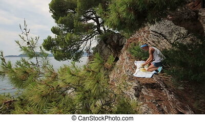 young blond woman having a picnic outdoor on the rock