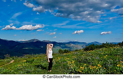 Young blond woman hiking in alpine meadows.