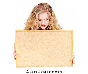 Young blond woman holding a cork board isolated on white and looking down on it
