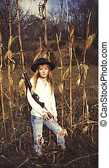 Young blond woman holding a gun and standing in a corn field